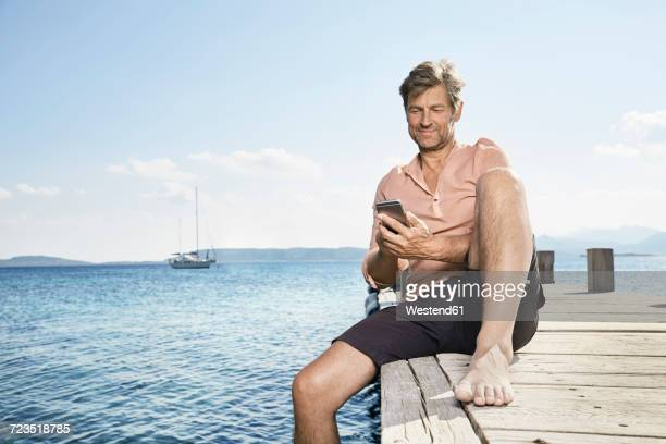 Smiling man sitting on jetty using cell phone