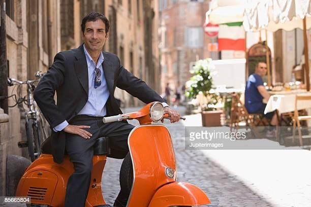 Smiling man sitting on motor scooter