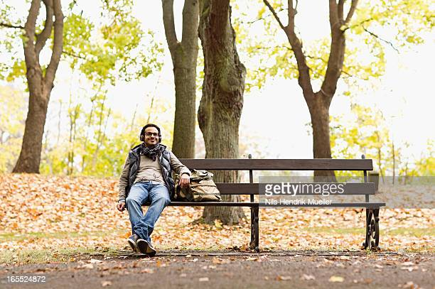 Smiling man sitting on park bench