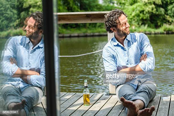 Smiling man sitting on platform at the waterside with beer bottle