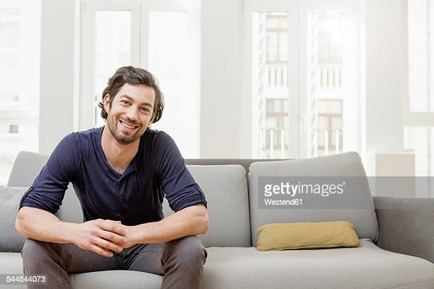 Smiling man sitting on sofa