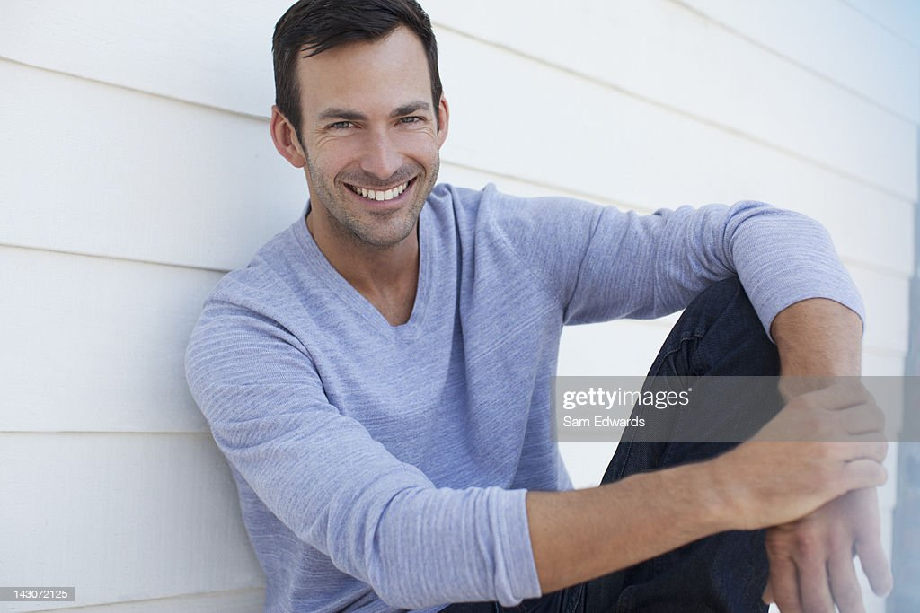 Smiling man sitting outdoors : Stock Photo