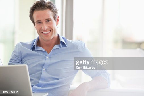 Smiling man sitting with laptop : Stock Photo