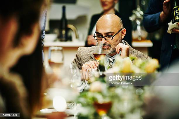 Smiling man smelling wine during dinner party