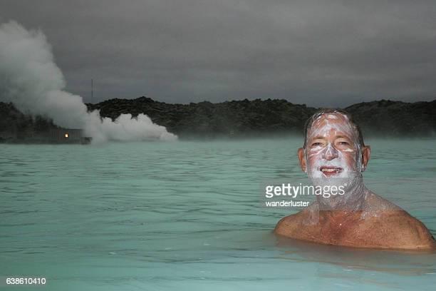 Smiling man soaking in hot springs