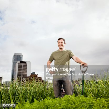 smiling man standing amongst greenery