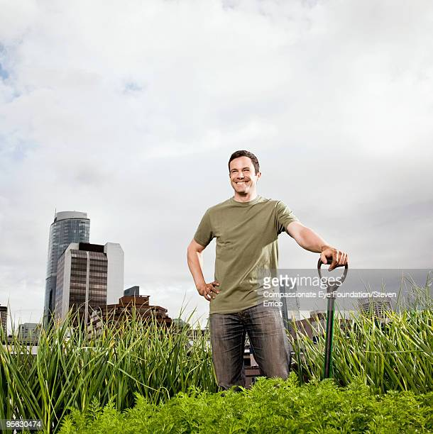 smiling man standing amongst greenery