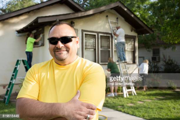 Smiling man standing as people paint house
