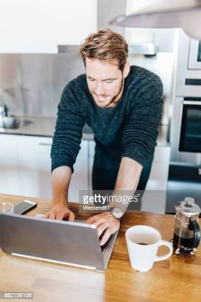 Smiling man standing in kitchen using laptop