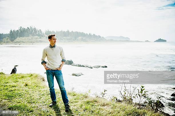 Smiling man standing on grass near ocean
