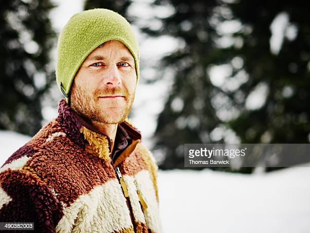 Smiling man standing outdoors in the snow