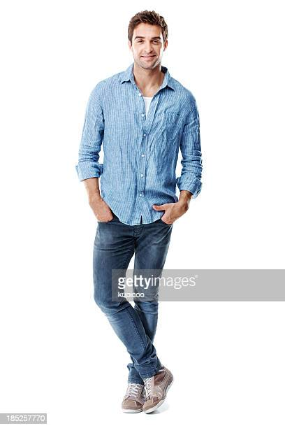 Smiling man standing with ankles crossed