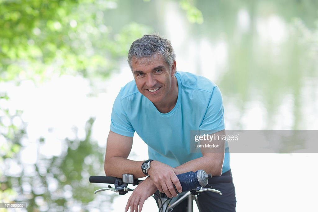 Smiling man standing with bicycle : Stock Photo