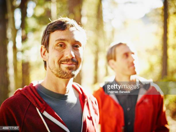 Smiling man standing with friend in forest