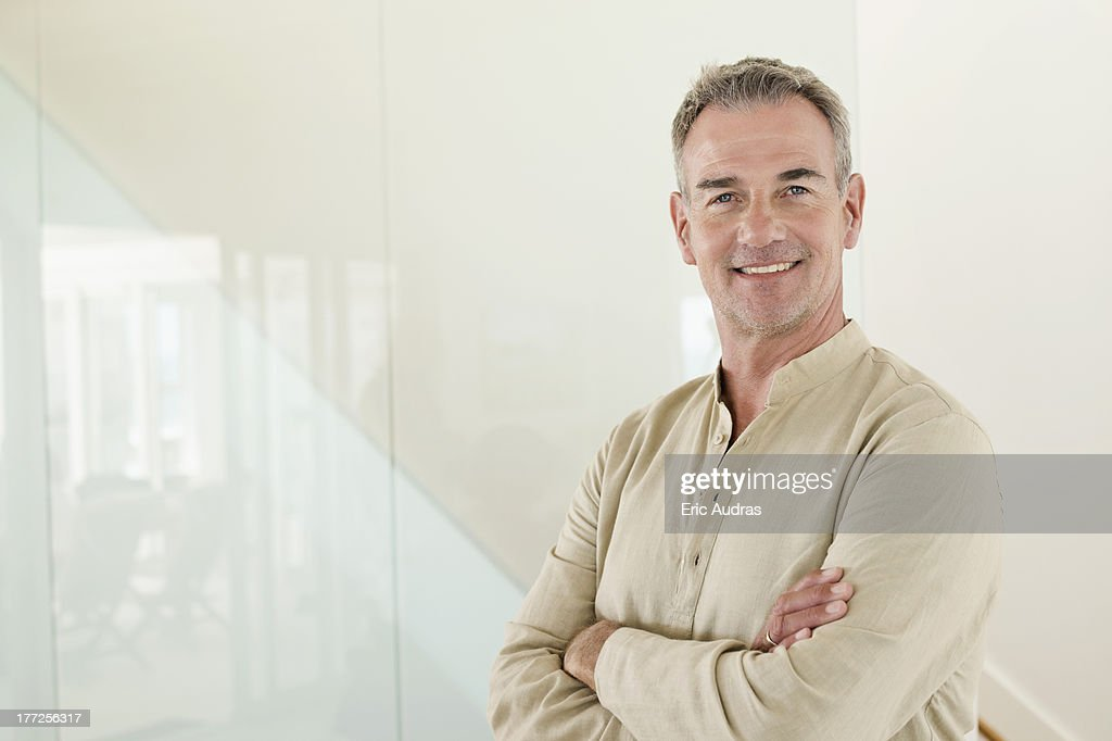 Smiling man standing with his arms crossed : Stock Photo