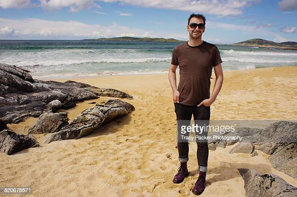 A smiling man stands on a Scottish Island beach
