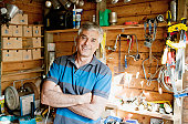 Smiling man surrounded by tools in workshop