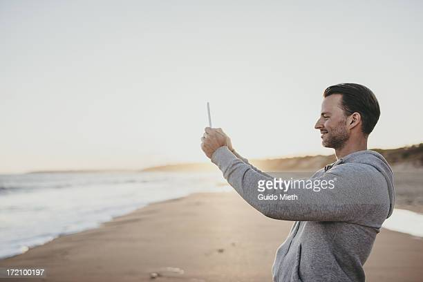 Smiling man taking pictures on beach.