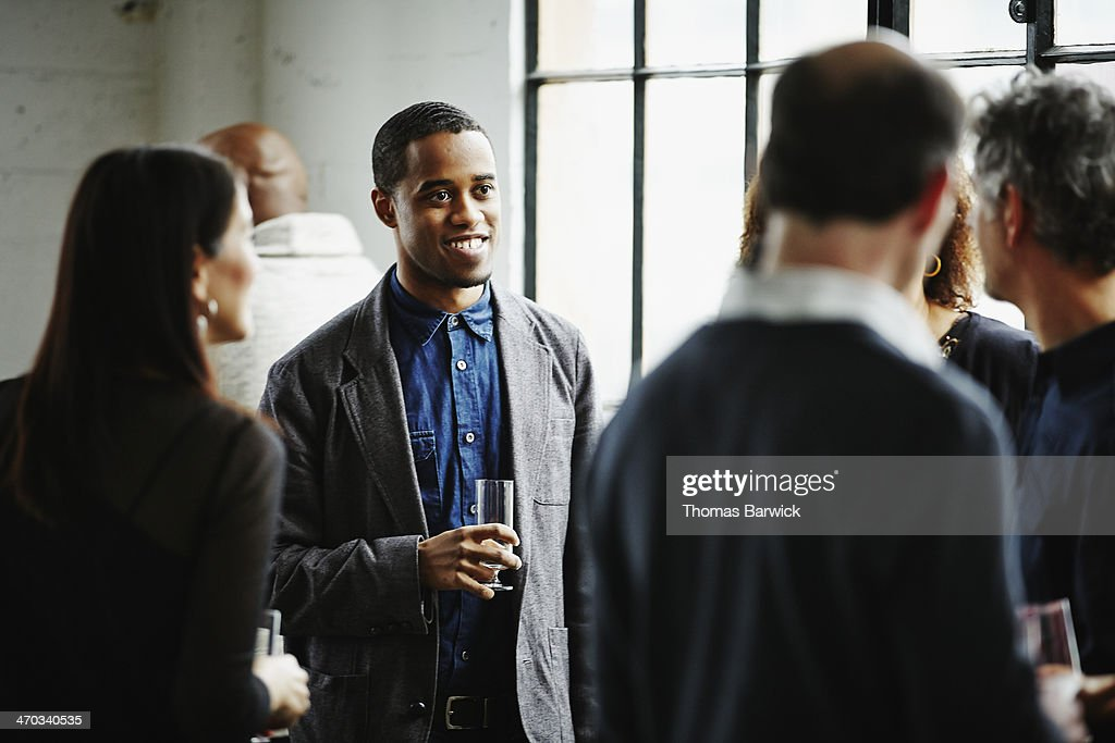 Smiling man talking with friends at dinner party : Stock Photo