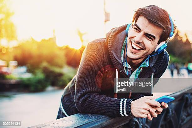 Uomo sorridente ricevere tweet e messaggi di testo e ascoltare musica