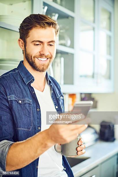 Smiling man texting through smart phone while holding coffee cup
