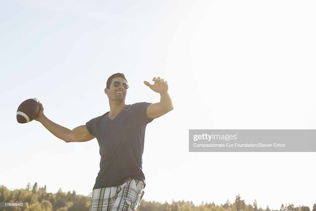 Smiling man throwing football outdoors