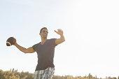 Smiling man throwing football outdoors