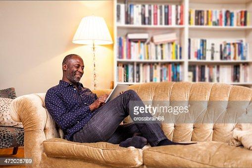 Souriant homme mature avec tablette numérique dans la salle de séjour