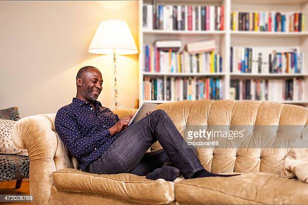 A smiling man using a digital tablet on his sofa
