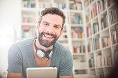 Smiling man using digital tablet in living room