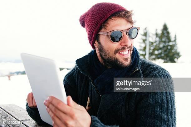 Smiling man using digital tablet.