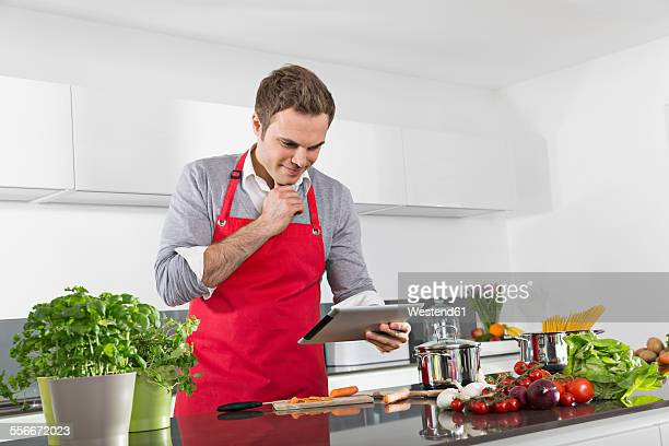 Smiling man using digital tablet while cooking
