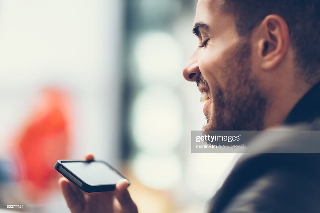 Smiling man using smartphone to watch tv