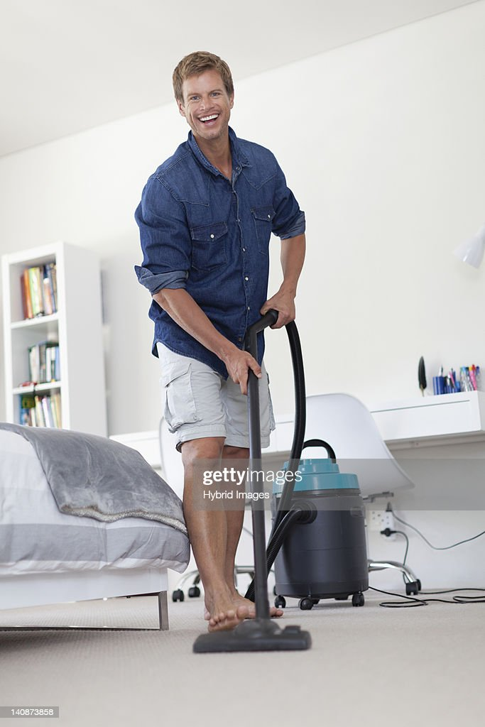Smiling man vacuuming living room : Stock Photo