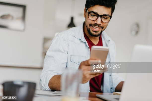 Smiling man with beard is using mobile phone