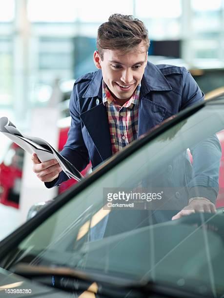 Smiling man with brochure looking at car in car dealership showroom