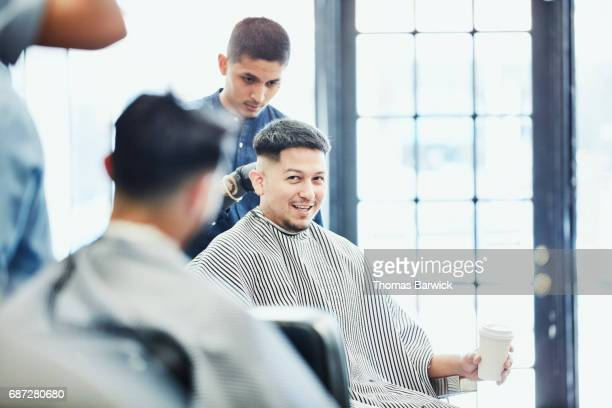 Smiling man with coffee cup in discussion with friend while having hair cut in barber shop