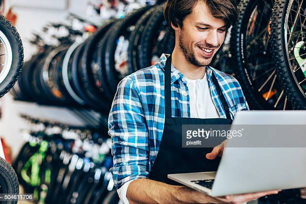 Smiling man with computer at bicycle shop