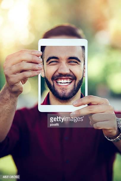 Homme souriant avec tablette numérique en selfie