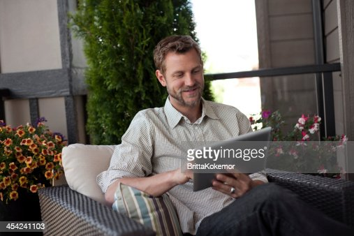 Smiling man with digital tablet sitting outside : Stock Photo