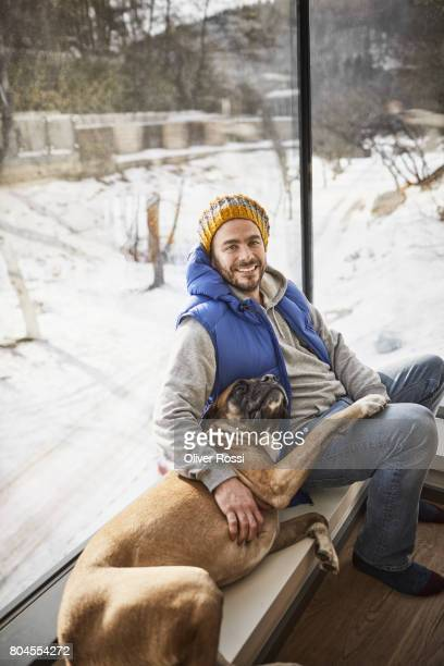 Smiling man with dog at the window