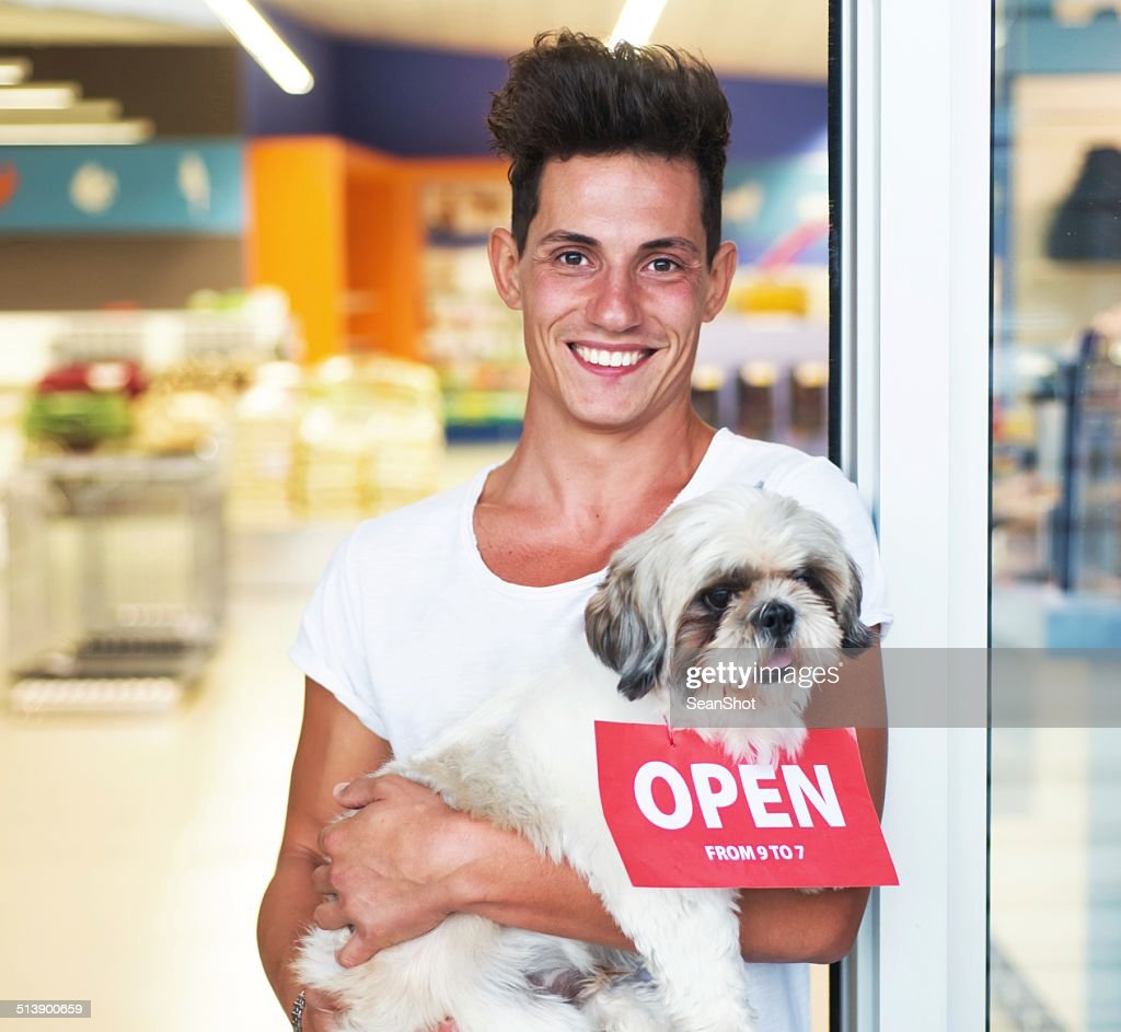 Smiling Man with Dog on Entry of a Pet Shop