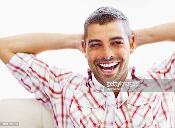Smiling man with hands behind head