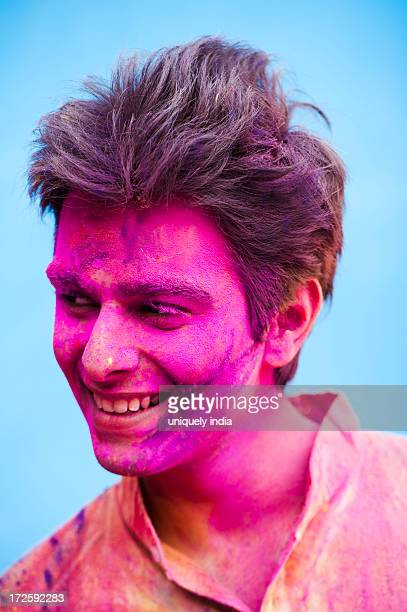 Smiling man with his face smeared with colors