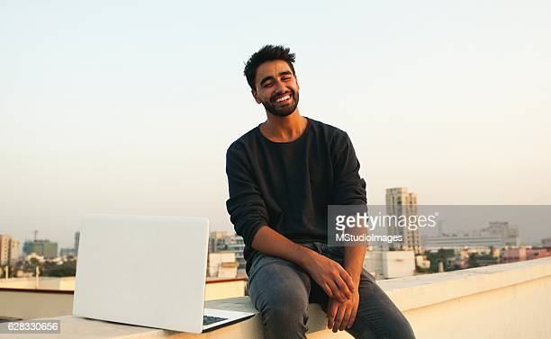 Smiling man with laptop on rooftop.