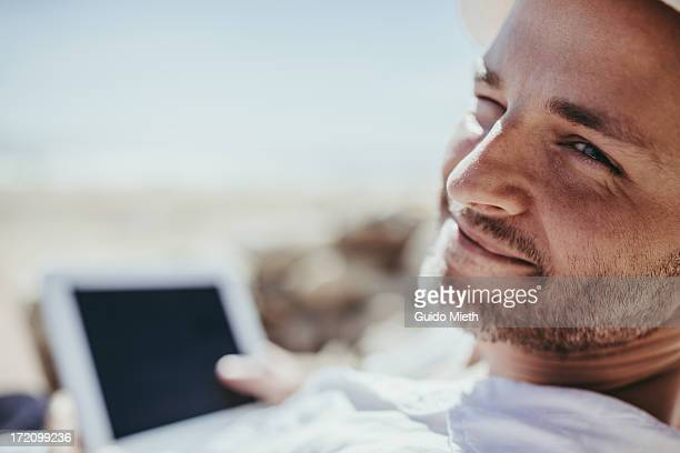 Smiling man with tablet pc on a beach.