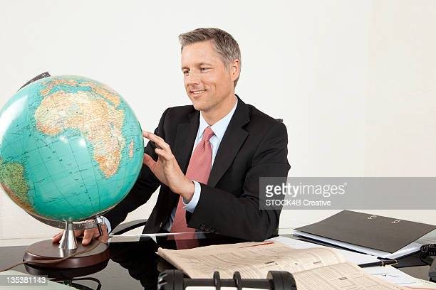 Smiling manager at desk looking at globe