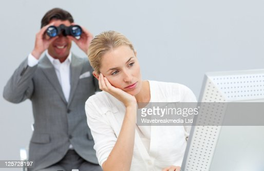 Smiling manager holding binoculars looking at his colleague's computer : Stock Photo