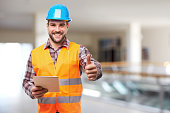 Smiling manual worker in blue helmet with digital tablet and gesture thumb up