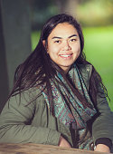 A young Maori woman in an outdoor setting looking at camera and smiling.